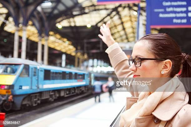 Girl waving at somebody in railway station
