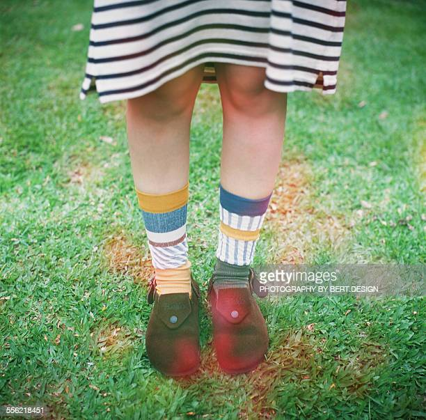 Girl wear different socks on the grass