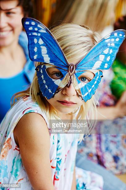 Girl wearing a butterfly mask.