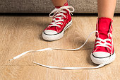 Little girl wearing a pair of red sneakers at home. A sneaker is untied