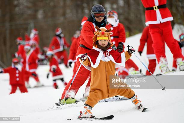 A girl wearing a reindeer costume enjoys skiing with her father in Santa Claus outfit at Mt Jeans Nasu on December 20 2014 in Nasu Tochigi Japan The...