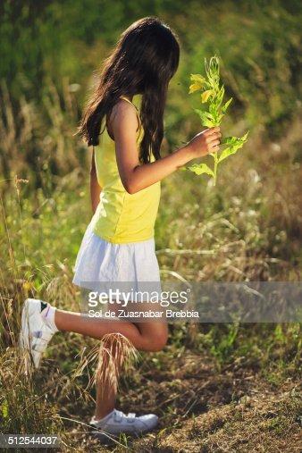 Girl wearing a short skirt walking with a flower