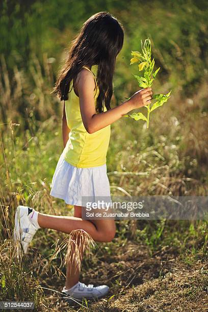 Girl wearing a short skirt walking with a flower