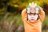 A girl wearing a Thanksgiving turkey headdress