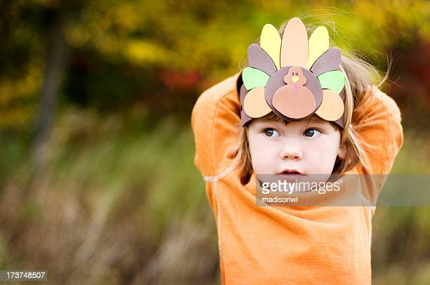 A girl wearing a Thanksgiving turkey headdress