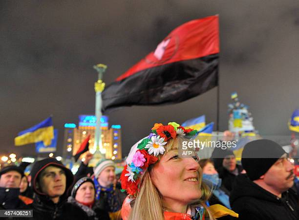 A girl wearing a traditional Ukrainian wreath attends a mass Ukrainian opposition rally on Independence Square in Kiev on December 17 2013 Russian...