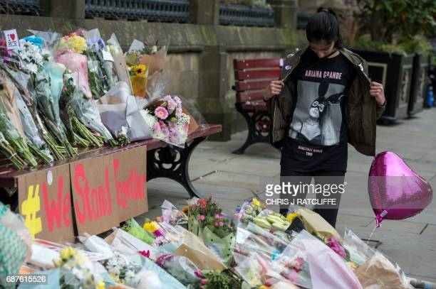 A girl wearing a tshirt from Ariana Grande's Dangerous Woman Tour poses for a photograph alongside flowers in Albert Square in Manchester northwest...