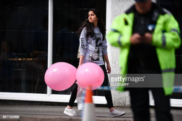 TOPSHOT A girl wearing a tshirt of US singer Ariana Grande carrying balloons from the Ariana Grande concert at the Manchester Arena leave a hotel in...