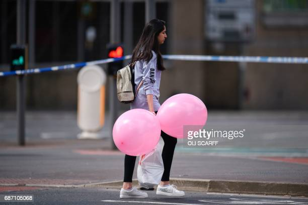 A girl wearing a tshirt of US singer Ariana Grande carrying balloons from the Ariana Grande concert at the Manchester Arena leave a hotel in...