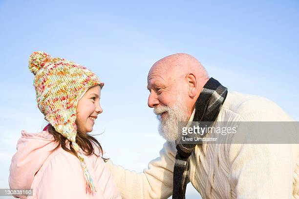 Girl wearing a woolen hat and her grandfather laughing at each other