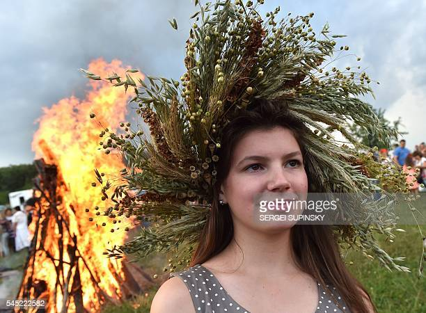 A girl wearing a wreath stands in front of a bonfire during celebrations of the Ivana Kupala night an ancient heathen holiday in the Pyrogove village...