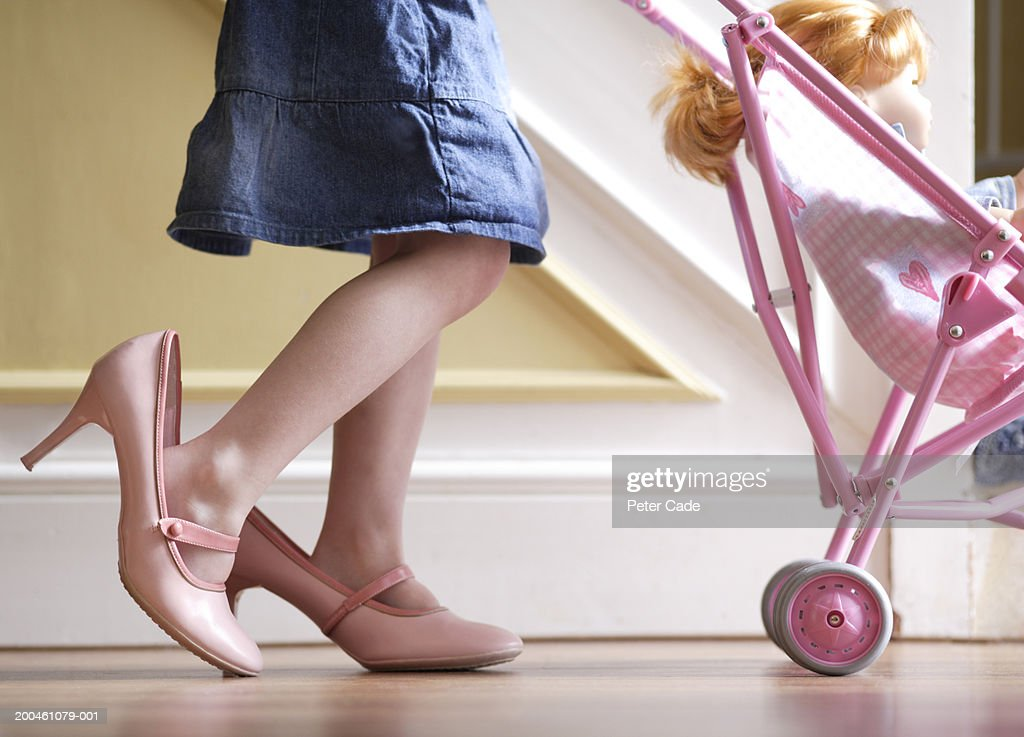 Girl (3-5) wearing adult shoes, pushing doll in pram, low section : Stock Photo