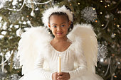 Girl (5-6) wearing angel costume, holding candle, Christmas tree in background, portrait