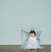 Girl (2-4) wearing angel costume sitting on floor, head in hands