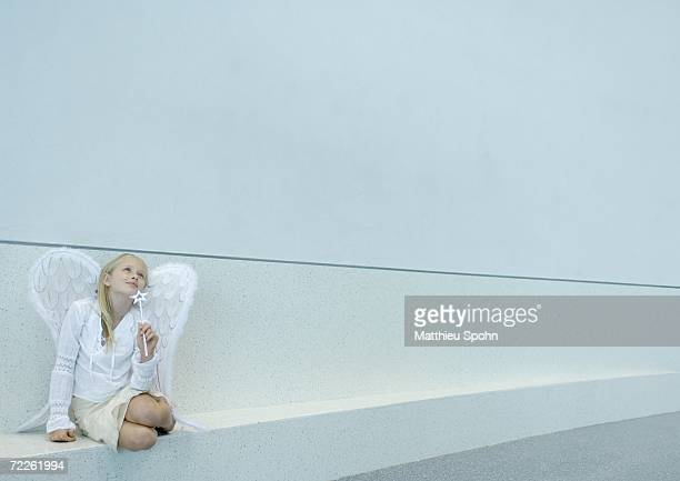 Girl wearing angel wings and holding wand