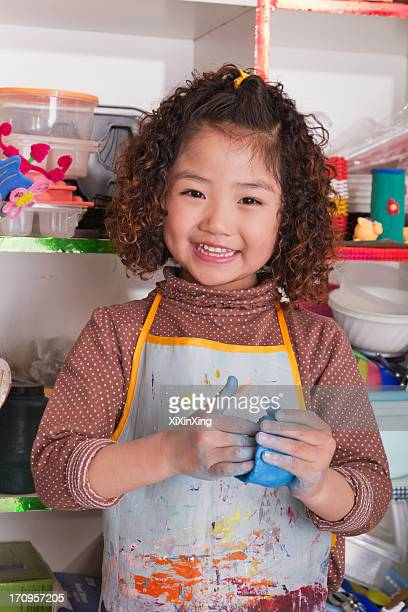 Girl Wearing Apron and Playing with Clay