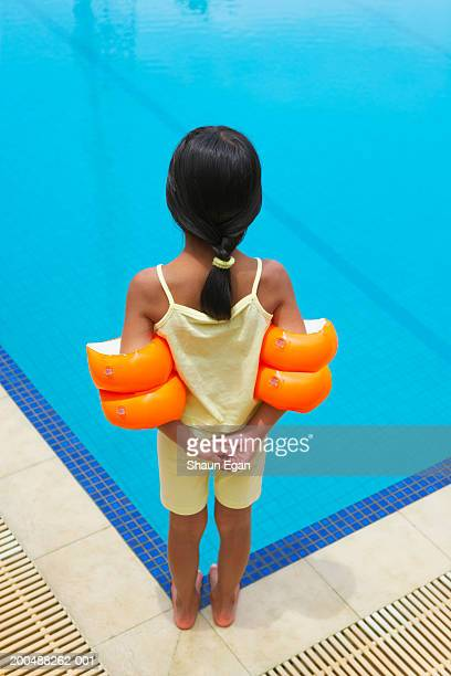 Girl (4-6) wearing arm bands by swimming pool, rear view