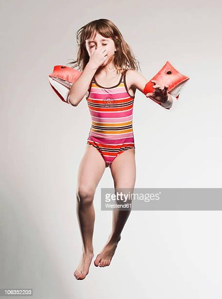 Girl (7-8) wearing armband and jumping