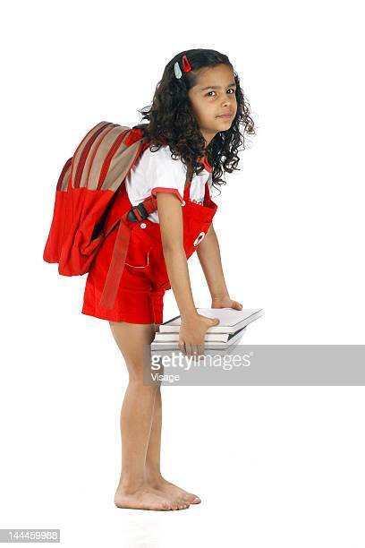 Girl wearing backpack carrying books