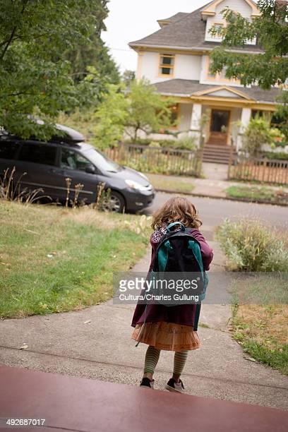 Girl wearing backpack walking down path