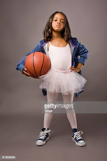 Girl wearing ballet outfit and holding basketball