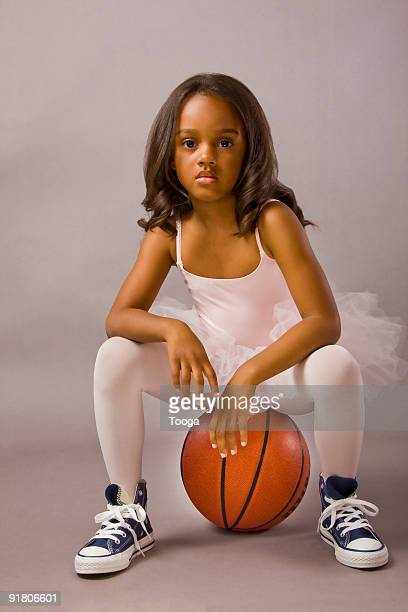 girl wearing ballet outfit sitting on basketball
