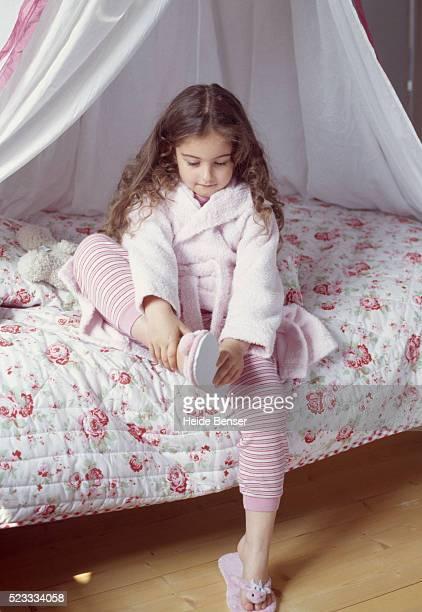 Girl wearing bathrobe sitting on bed