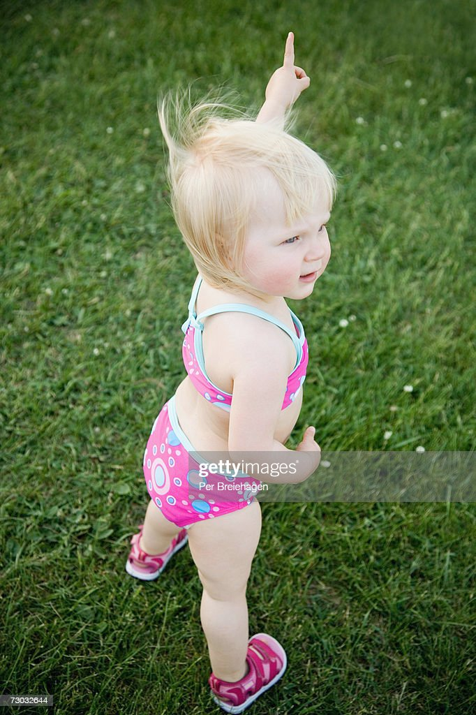 Girl (21-24 months) wearing bikini standing on grass, elevated view