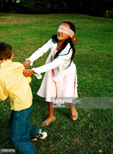 Girl wearing blindfold playing with her friend (4-8)