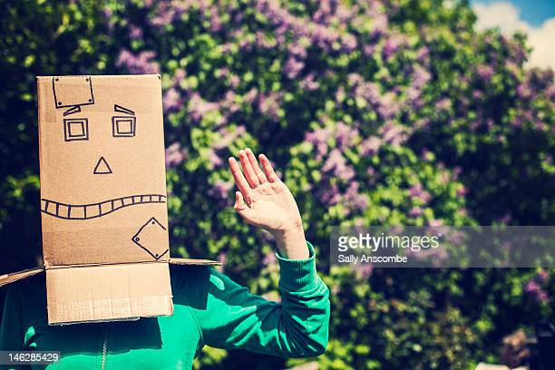 Girl wearing box with robot face on her head
