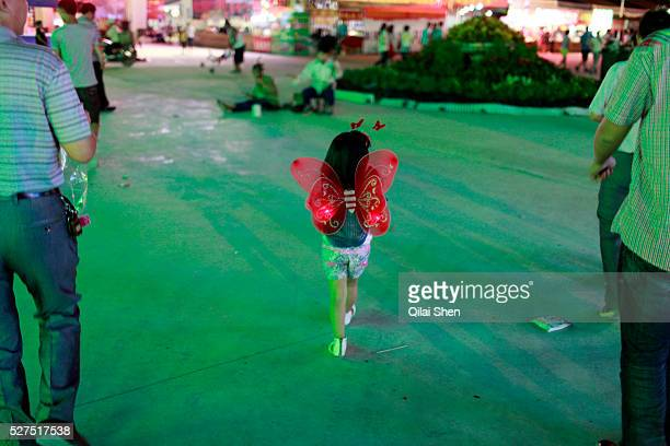 A girl wearing butterfly wings walks through the carnival grounds of the Qingdao Beer Festival in Qingdao China on 27 August 2011 Named after the...
