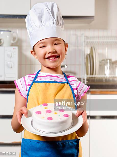Girl (6-7) wearing chef's hat presenting cake in kitchen
