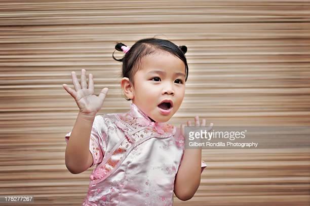 Girl wearing cheongsam looking surprised