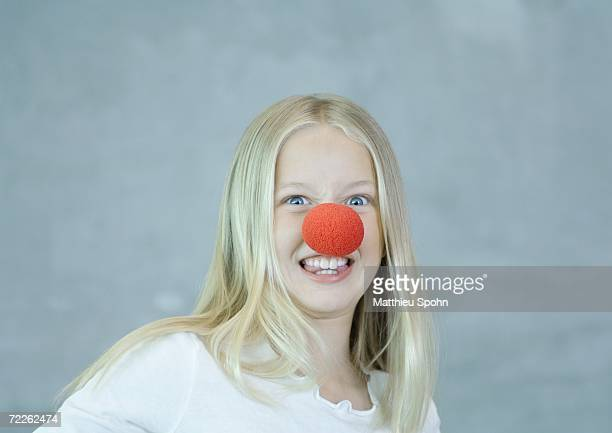 Girl wearing clown nose and making face