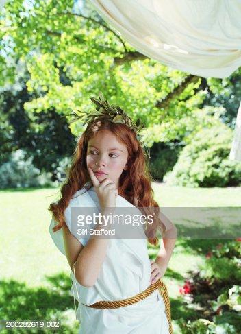 Girl (7-9) wearing costume in garden