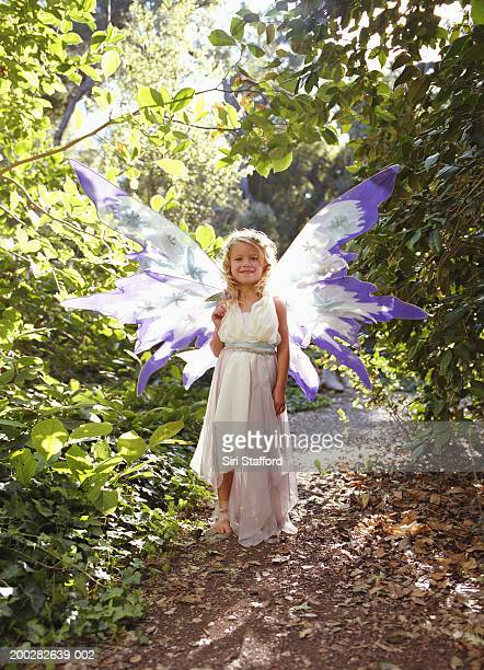 Girl (4-6) wearing costume with wings, outdoors