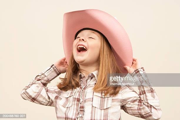 Girl (5-7) wearing cowboy hat, head back, singing