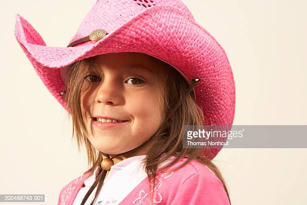 Girl (5-7) wearing cowboy hat, smiling, portrait