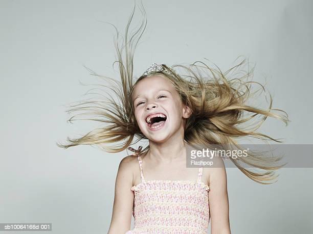 Girl (6-7) wearing crown, laughing, close-up