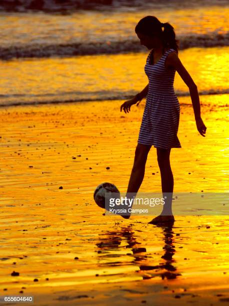 Girl wearing dress playing at the beach sunset