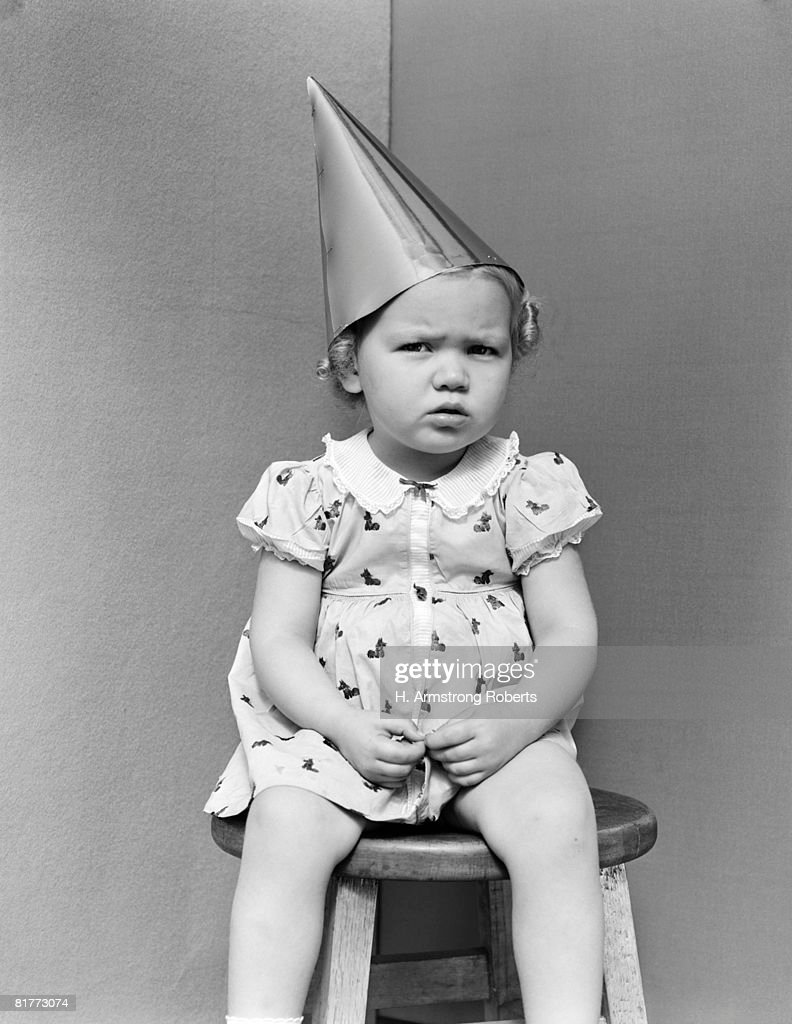 Girl Wearing Dunce Cap Sitting On Stool In Corner Unhappy Punishment Angry. : Stock Photo