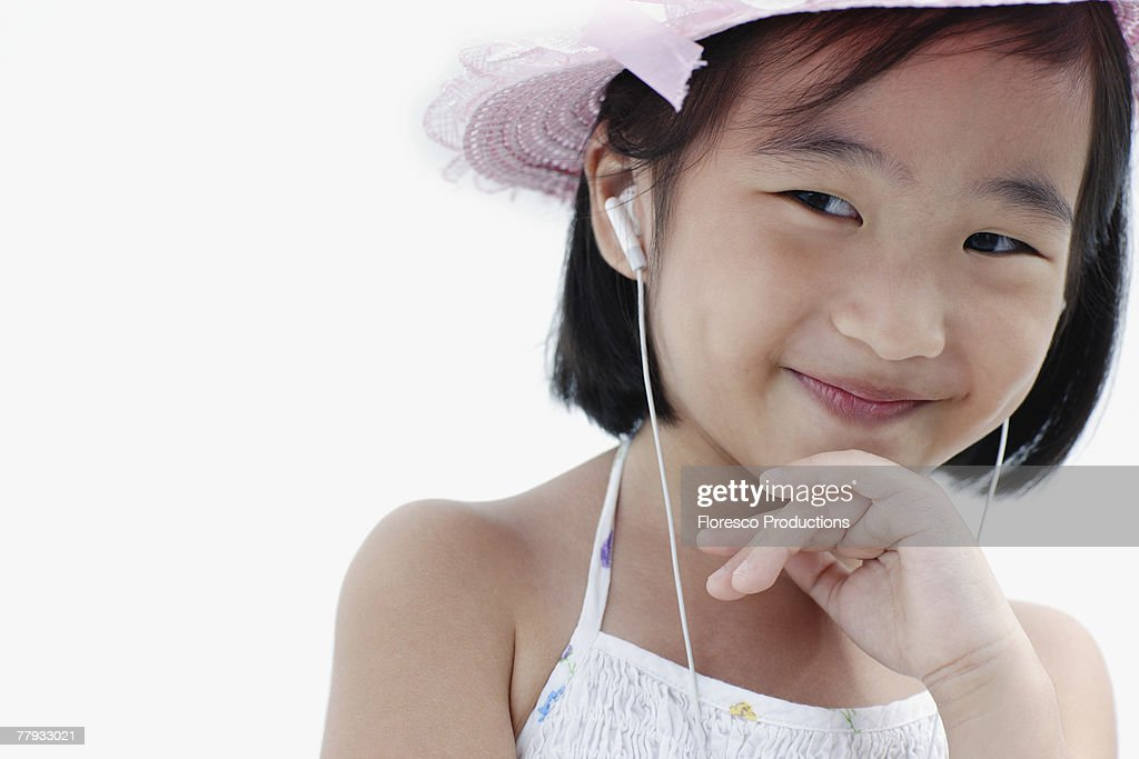 Girl wearing earbuds and hat smiling : Stock Photo