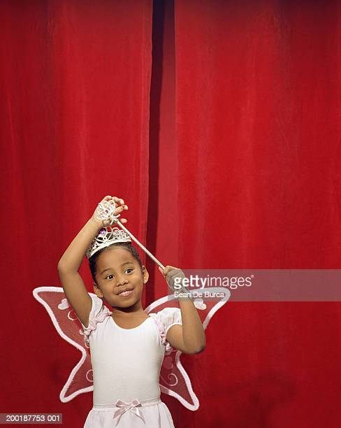 Girl (5-7) wearing fairy costume in front of red curtain