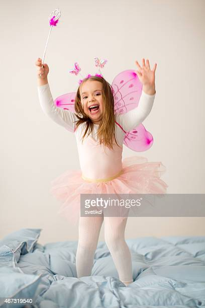 Girl wearing fairy costume jumping on bed.