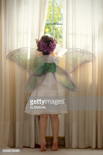 Girl (6-7) wearing fairy costume looking out of window