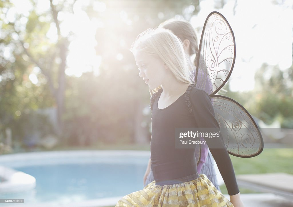 Girl wearing fairy wings in backyard : Stock Photo