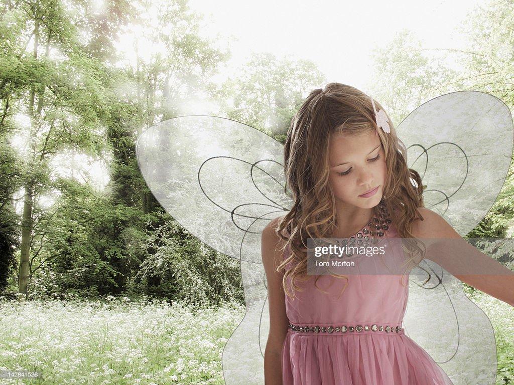 Girl wearing fairy wings in field of flowers