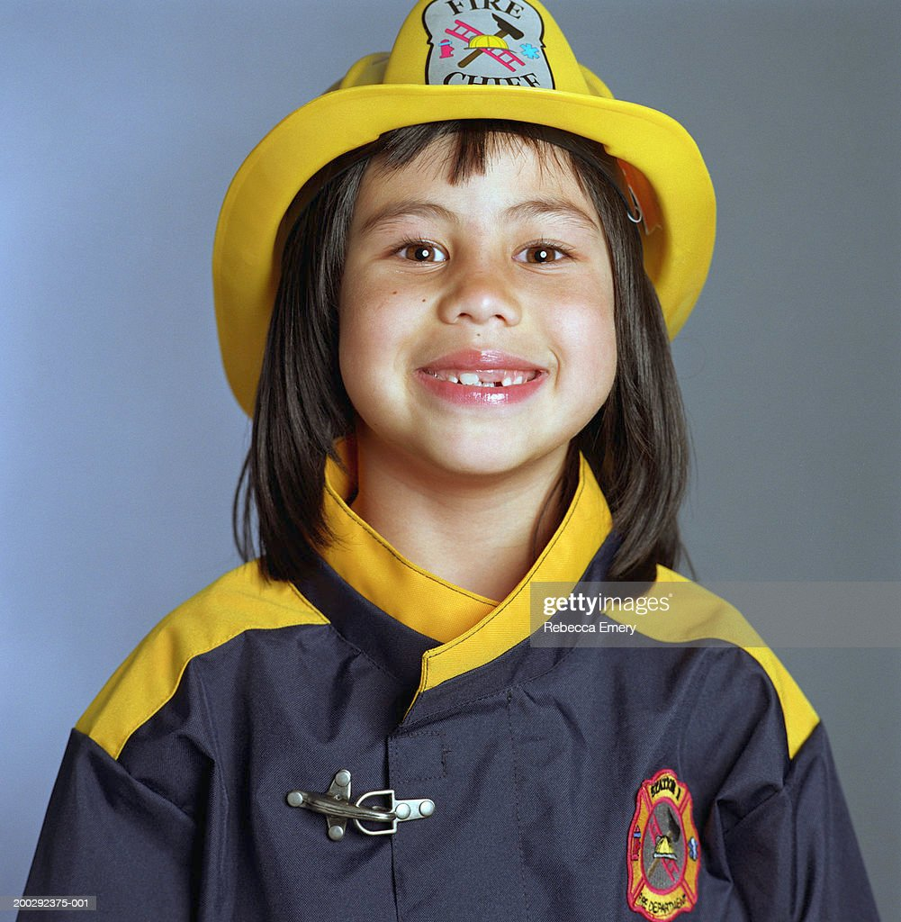 Girl (5-7) wearing firefighter costume, smiling, portrait