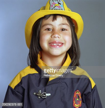 Girl (5-7) wearing firefighter costume, smiling, portrait