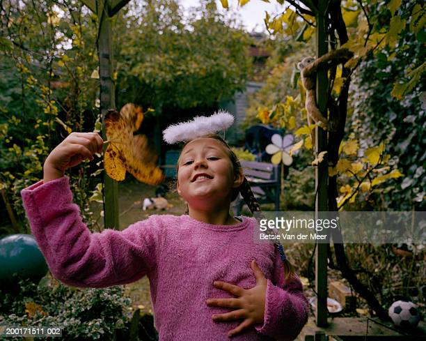 Girl (7-9) wearing fluffy halo, fanning herself with leaf, portrait